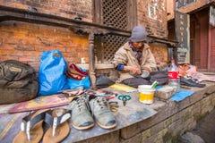 鞋匠在街道上工作 社会等级体系是原封今天,但是规则不是一样刚性的,象他们是从前 免版税库存照片