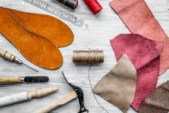 鞋匠工作地点  皮肤和工具在灰色木书桌b上 免版税库存图片