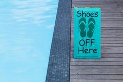 鞋子不由在木地板上的游泳池签字以绿色 免版税库存图片