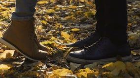鞋子特写镜头在叶子的报道了地面,到达男朋友的女孩对亲吻,日期 影视素材