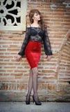 黑鞋带女衬衫、红色裙子和高跟鞋的迷人的年轻深色的妇女在砖墙附近。性感的华美的少妇 免版税库存照片