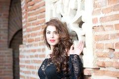 黑鞋带女衬衫的迷人的年轻深色的妇女在红砖墙壁附近。有长的卷发的性感的华美的少妇 库存图片