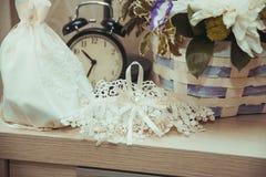 鞋带婚礼袜带和新娘的白色提包是我们桌在闹钟附近 免版税库存照片