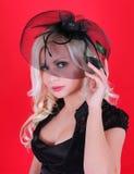 鞋带帽子的美丽的白肤金发的少妇在红色 库存图片