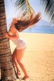 鞋带接触棕榈风的白肤金发的女孩向上举长的头发 库存照片