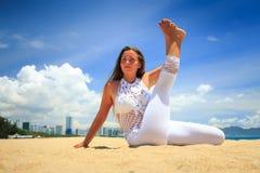 鞋带的女孩在瑜伽asana舒展了在海滩的腿正面图 库存图片
