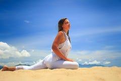 鞋带的白肤金发的女孩在瑜伽asana在海滩留下腿舒展 库存图片
