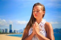 鞋带的白肤金发的女孩在瑜伽asana雷电坐海滩 库存图片