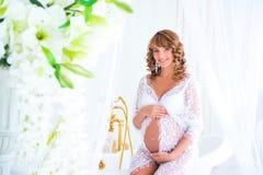鞋带褂子的妊妇在有花的花瓶附近 库存图片