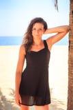 黑鞋带连衣裙的亭亭玉立的女孩在海滩的棕榈倾斜手肘 免版税库存图片