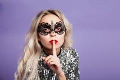 鞋带面具的性感的白肤金发的女孩投入了手指到她的嘴唇 文本的空间 免版税库存照片