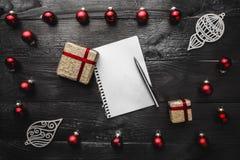 鞋帮、上面、看法从上面红色常青玩具,礼物、手工制造冬天小雕象、笔记薄和笔在黑背景 库存照片