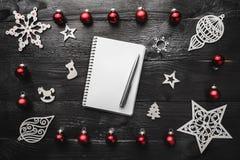 鞋帮,上面,看法从上,木冬天小雕象,红色戏弄笔记薄和笔在黑背景 免版税库存照片