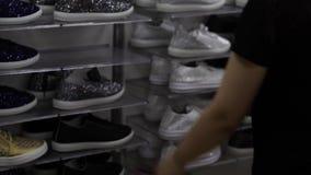 鞋店的一名妇女,选择运动鞋 妇女买在精品店的鞋子 股票视频