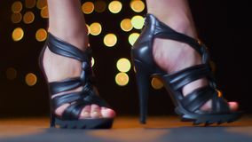 鞋类,显示她的高跟鞋的妇女令人敬畏的英尺长度在移动的照相机严密地站立和紧密,明亮 股票录像