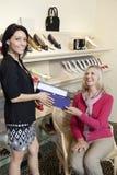 给鞋类箱子的一位中间成人推销员的画象鞋店的成熟女性顾客 免版税库存照片