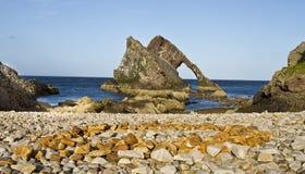 鞠躬无意识而不停地拨弄岩石有广角看法, Portknockie,苏格兰 库存图片