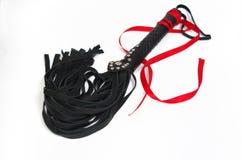 黑鞭打的鞭子和红色丝带 免版税库存图片