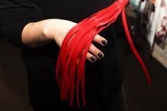 鞭打红色,性玩具在女性手上 免版税库存照片