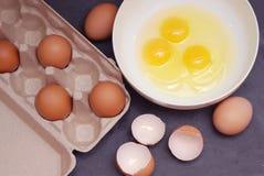 鞭打鸡鸡蛋 在杯的卵黄质和蛋蛋白质 食物和鸡鸡蛋的准备 在切板的蛋壳 顶视图 免版税图库摄影