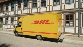 韦尔尼格罗德,德国, 2018年5月:邮政局敦豪航空货运公司的无盖货车在一条静街上站立在的德国镇 免版税库存图片