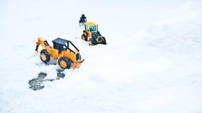 韩国冬天,许多白色雪,冰冷的路,两辆大玩具铲车 库存照片