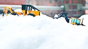 韩国冬天,许多白色雪,冰冷的路,两辆大玩具铲车 免版税图库摄影