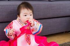 韩国女婴叮咬丝带 免版税库存图片