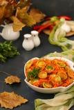 韩式沙拉用绿色蕃茄和红萝卜在一个白色色拉盘在黑暗的背景 库存图片