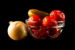 韭葱和盐味的黄瓜用蕃茄在玻璃花瓶 葱和碗红色蕃茄和黄瓜,隔绝在黑背景 库存图片