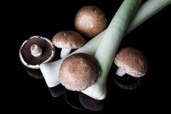 韭葱和蘑菇在黑色从上面 库存图片