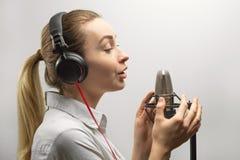 音乐、演艺界、人们和声音概念-有耳机和话筒的歌手唱一首歌曲的在录音室, 免版税库存照片