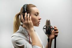 音乐、演艺界、人们和声音概念-有耳机和话筒的歌手唱一首歌曲的在录音室, 免版税图库摄影