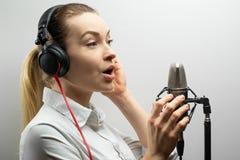 音乐、演艺界、人们和声音概念-有耳机和话筒的歌手唱一首歌曲的在录音室, 免版税库存图片