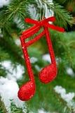 音乐与音乐笔记的xmas背景关于与雪的一个树枝 免版税库存照片