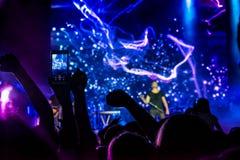 音乐会人群 在后面照的人剪影由明亮的蓝色和紫色阶段光 在五颜六色的阶段光的欢呼的人群 r 免版税库存图片