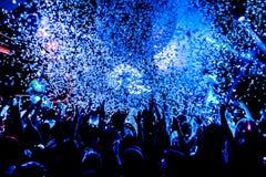 音乐会剪影在与五彩纸屑的明亮的阶段光前面拥挤 免版税库存照片