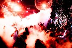 音乐会剪影在与五彩纸屑的明亮的阶段光前面拥挤 库存照片