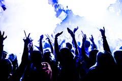 音乐会剪影在与五彩纸屑的明亮的阶段光前面拥挤 免版税图库摄影