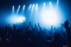 音乐会剪影在明亮的阶段光前面拥挤 人群的未被认出的人 复制空间背景 爱好者a人群  库存照片