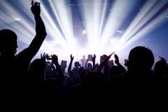 音乐会剪影在明亮的阶段光前面拥挤 在纸的和平主义标志 免版税库存图片
