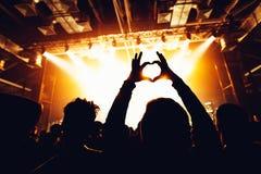 音乐会剪影在明亮的阶段光前面拥挤 显示心脏标志的人们 做心形的h的观众的手 免版税图库摄影
