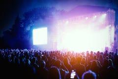 音乐会剪影在明亮的阶段光前面拥挤 免版税库存照片