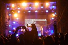 音乐会射击录影或照片的人们 库存图片