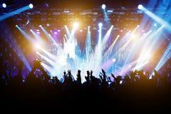 音乐会的满意的人,从阶段的色的光 免版税库存图片