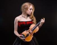 音乐会礼服的白肤金发的女孩有小提琴的 免版税库存照片