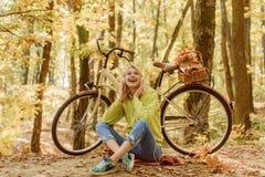 音乐停留 金发碧眼的女人享用放松森林温暖的秋天 有自行车和耳机的女孩 有自行车秋天的妇女 库存照片