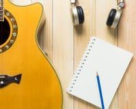 音乐写歌设备,写歌的空白的书吉他耳机 库存照片