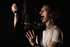音乐和创造性 一件T恤杉的英俊的年轻人,有一把电吉他的,在黑色被隔绝的backgro伸出他的舌头, 库存图片