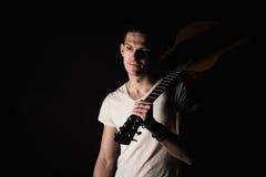 音乐和创造性 T恤杉和牛仔裤的英俊的年轻人站立与在他的肩膀的一把声学吉他,在黑孤立 免版税库存照片